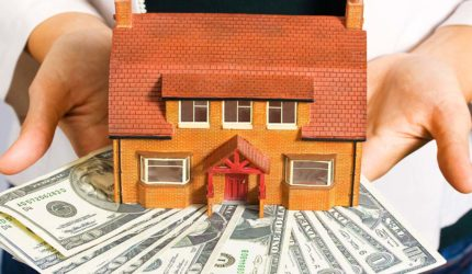 a-person-holding-a-miniature-house-and-some-dollar-bills